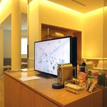 One of the TVs in the room and complimentary mini bar