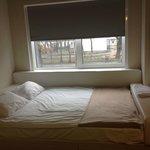 кровать возле окна с видом на детский садик