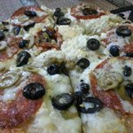 White pizza with black olives and pepperoni