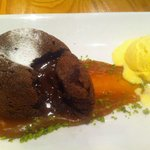 Molten chocolate pudding with salted caramel sauce, cardamom ice cream and crushed pistachios