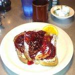 Cream cheese stuffed french toast a la raspberry sauce.