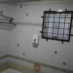 Решетка на окне в ванной, оторванная железная вешалка, диспенсер с мылом
