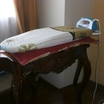 The ironing board on top of two pillows on top of a sideboard