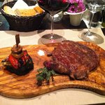 Ribe eye steak served on custom olive wood made plate