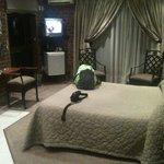 Luxury Suite bed, minibar and courtyard door