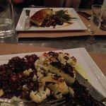 Cauliflower steak and Cod dish across table