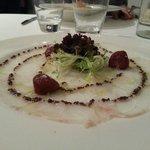 Carpaccio de bacalao con tomates secos y aceite de oliva negra