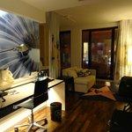 La mesa de trabajo y el sofa en frente de la tv plana