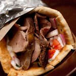 Greek spiced Leg of Lamb, baked nightly! Seen here as a Wrap with Tzatziki, onions & tomato