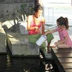Im Eingangsbereich schwimmen Koi in einem Teich. Hier hilft meine Tochter Koong beim füttern.