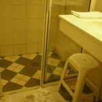 el baño con las toallas en el suelo, tal como lo había dejado