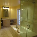 Bathroom with two vanity areas, a whirlpool tub, and steam shower