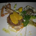 Tartare di tonno all'arancio e lime su verdure croccanti con ostrica al naturale e scampo marina