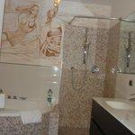 Clean tiled bath comes with original l art work