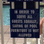 Sign at pool saying not to save chairs