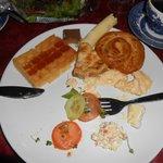 Um café da manhã farto com frutas e comidas típicas.