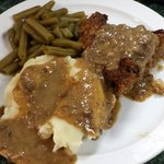 Meatloaf with mashed potatoes and gravy and green beans.