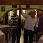 Официант Василис держит свежую рыбу-меч, владелец заведения дослеживает за ним)