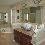 The bathroom Boasts a Jacuzzie tub, shower, and a two person vanity