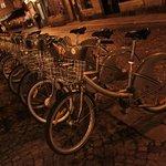 Rua próxima, sempre com bicicletas e carros elétricos carregando.