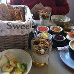 Fruta, granola, cesta de panes y cuencos dulces