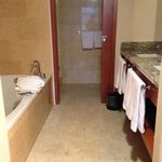Bath tub and sinks. Through the doorway is the toilet and stand up shower.