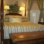 Magnolia guest room with cherry four poster bed and antique blanket chest