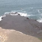 People surfing, beautiful volcanic rock