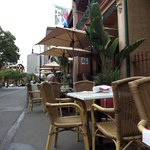Street view. The tables and chairs are set in to a normal front yard type space, and the footpat