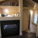 gas fireplace next to steps to bedroom