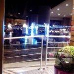 Parte interna do restaurante refletida na janela que tem vista para o rio.