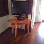 Big flat screen TV and fun orange furniture