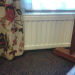Curtains covering the radiator, blocking the heat