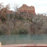 View of red rocks from inside hot tub overlooking infinity pool
