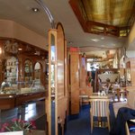 Inside of the restaurant; clean with dining area and a bakery.