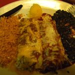 closeup of beef and chicken enchilada with black beans