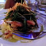 Garides (grilled prawns) with arugula salad and potato strings atop and zucchini cake beneath