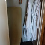 Closet with ironing board and bathrobes