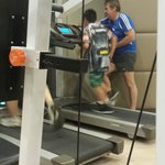 Gym on the 3rd floor. Dad and son working out.