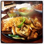 Sizzling mixed fajitas with chicken shrimp and steak soooo good!!