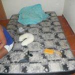colchão no chão e roupa de cama suja