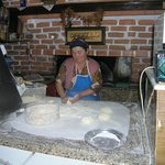 Bread being prepared for baking in oven behind
