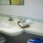 Bathroom with complimentary toothe brushes and a single small bar of soap.