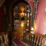 楼梯间,挂毯、彩绘玻璃、木雕的狮子柱头、古老的吊灯