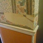 Ripped wallpaper in corridor