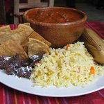 a meal with fried beans, rice, a tamal and mixed beef in sauce