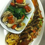 Grilled and stuffed European Seabass served with manilla clams + spinach