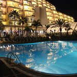 Hotel front and pool by night