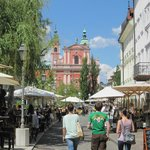 Lively cafe scene beside Ljubljanica river looking towards Triple Bridge and Franciscan church