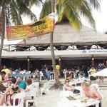Tavolini sulla spiaggia e ingresso del locale con la grande palapa (tetto di foglie di palma)